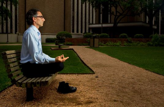 Photo By Cody Duty.  Dr. Lorenzo Cohen of M.D. Anderson meditates outside of M.D. Anderson's Cancer Prevention Building.